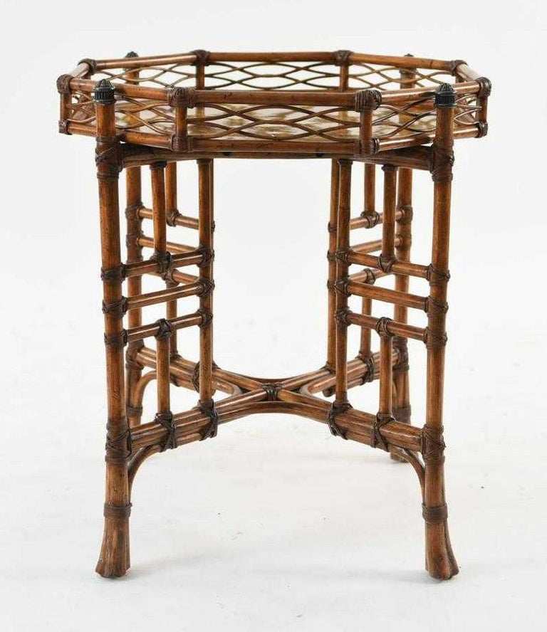 Stylish faux bamboo table is composed of a octagonal shaped gallery tray atop a crisscross base. The top features a faux inlaid surface while both the top and base are faux bound with simulated raffia. The table enhances any room with glamorous