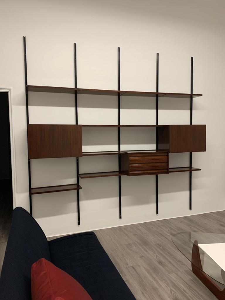 20th century Osvaldo Borsani 'E22' modular bookcase in rosewood and metal tracks, with ten (10) shelves and three (3) storage units: one with drawers and two with doors. Production Tecno, 1970s, Italy.