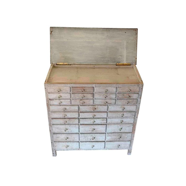 Early 20th century country apothecary or general store cabinet with 30 graduated drawers below a lift-top enclosing a shallow storage area. In original white paint, retaining it's original faceted glass drawer pulls, and having drawers with beveled
