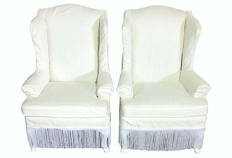 20th Century Pair Of American Queen Anne Style Wood Frame Upholstered Slip Cover Wing Back Arm Chairs. Features the original upholstery fabric in tact with newly made white denim and satin fringe detail slip covers. The mahogany legs are lacquered