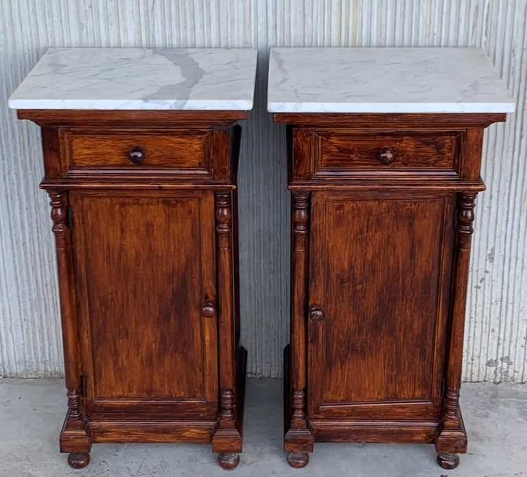 Pair of antique Biedermeier style bedside cabinets, late 19th-early 20th century, possibly French or Spanish, each in oblong rectangular form, the marble atop a fabric-lined surface, over a conforming case fitted with a single drawer over a cabinet