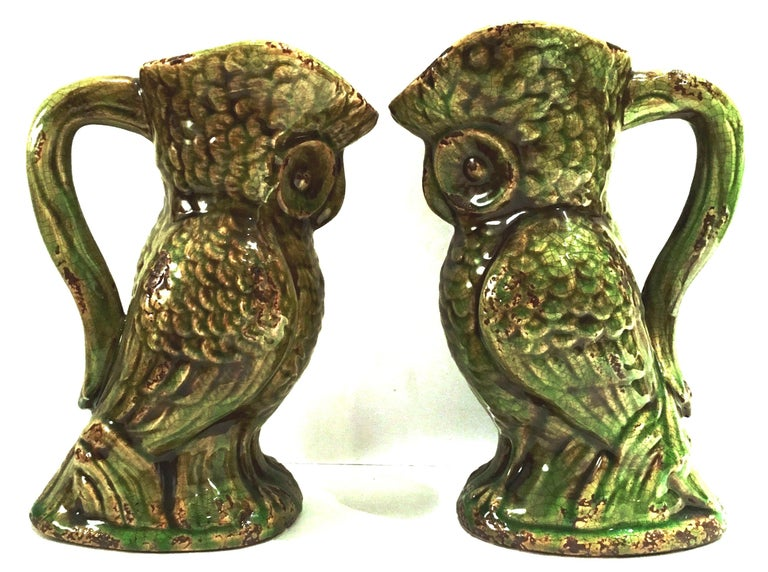 20th century pair of ceramic glaze handled owl beverage pitchers. Finished in a green and brown faux aged patina.