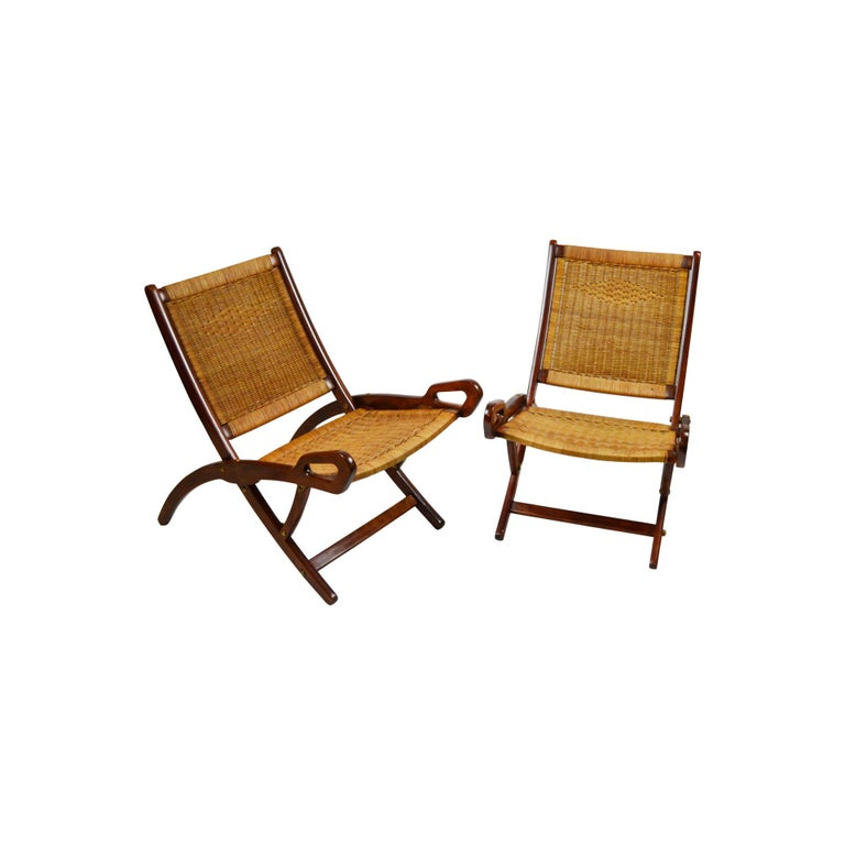Pair of folding armchairs designed by Gio Ponti in 1950s for Brothers Reguitti Production. The two armchairs have a wood structure and the seat and backrest in woven rush, details in brass. Very good condition. Presence of the brandmark