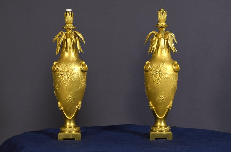 20th century pair of French chiselled and gilt bronze lamps Measurements: cm height 50 x diameter 13; base 9 x 9 cm. With the lampshade the lamp is 73 cm high  The particular pair of lamps was made in finely chiselled and gilt bronze in France at