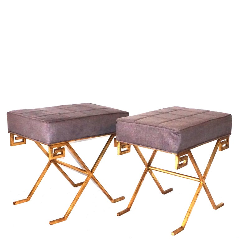 A vintage Art Deco pair of French gilt iron benches, upholstered with seat support on an X-form base with a Greek key design. Designed by Jean Michel Frank, in good condition. Wear consistent with age and use, circa 1920-1935, France.  Jean-Michel