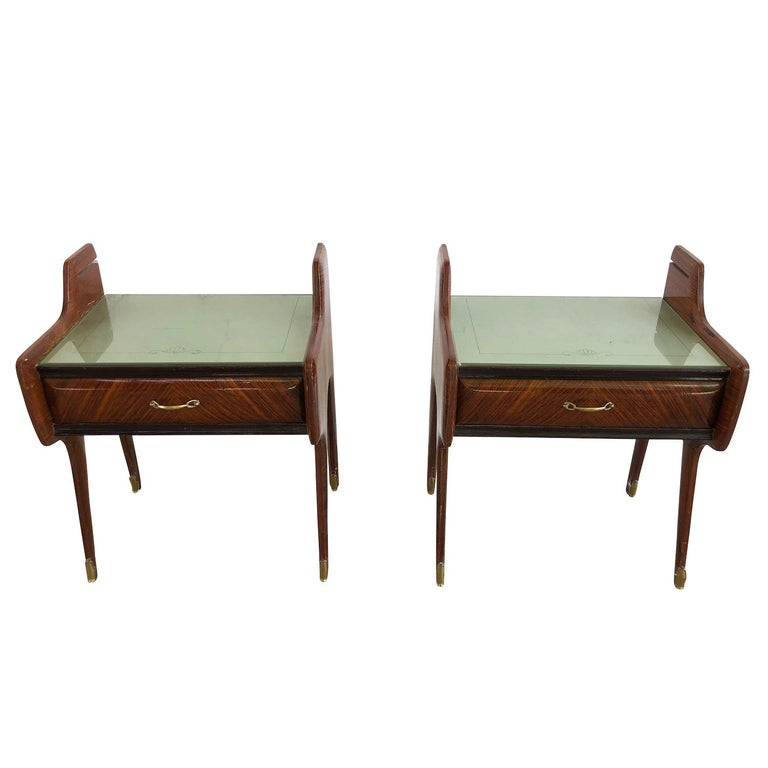 A pair of ebonized Mid-Century Modern nightstands or side bed tables with one drawer and lacking glass shelves, enhanced by very detailed brass handles, supported on tapered legs. Designed by Paolo Buffa. Wear consistent with age and use, circa