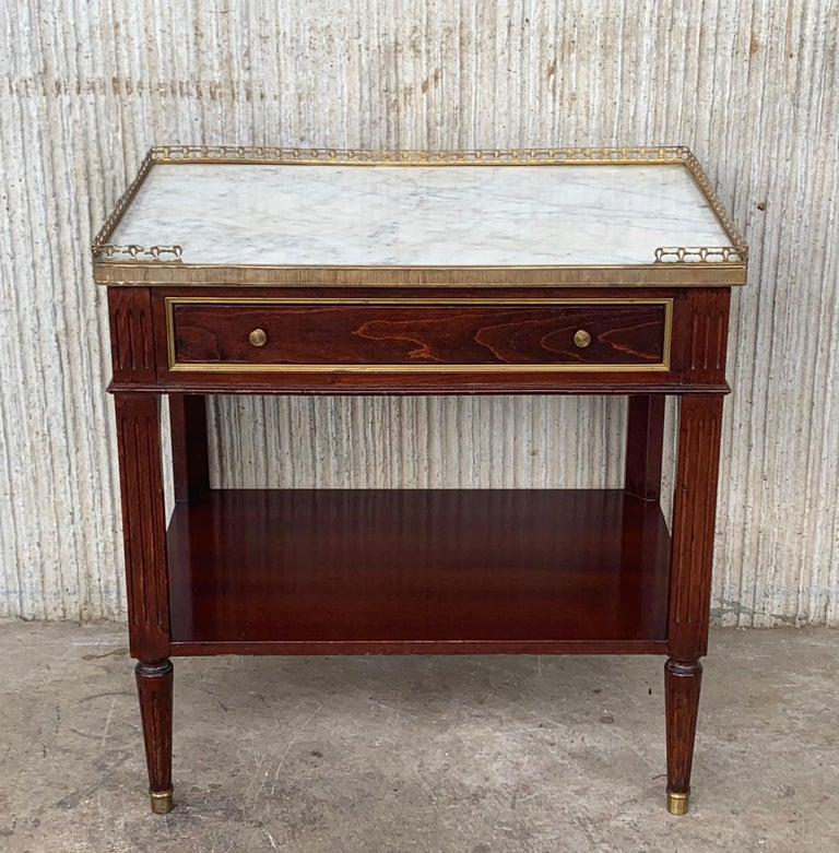 Antique Bouillotte French Louis XVI style pair of nightstands topped with a white marble and bronze crest, fluted legs finished with golden bronze clogs. One dovetailed small drawer with two brass pulls.  Measure: Height to the low shelve: 8.26in.