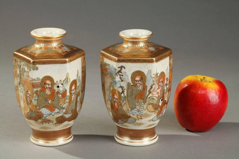 Two porcelain hexagonal Satsuma vases painted in polychrome enamels and gold. The paunch is decorated with intricate Japanese characters in a landscape, the neck and the shoulder with geometric patterns. Each vase features Satsuma mark in Japanese