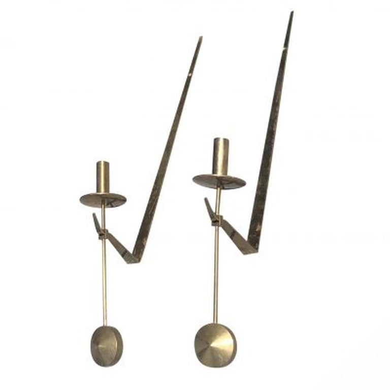 A wall-mounted pair of candleholders made out of brass by Pierre Forsell for Skultuna. Wear consistent with age and use, circa 1950-1960, Sweden Scandinavia.  Pierre Forsell was a Swedish silversmith and designer born in 1925 Stockholm, Sweden and