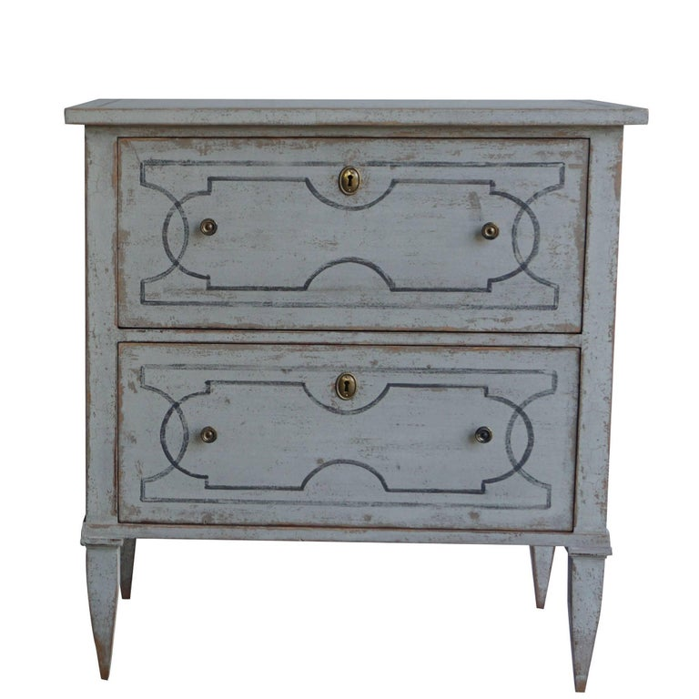 An antique pair of Swedish Gustavian chests made of hand carved pinewood and brass with two drawers, in good condition, perfect to be used as nightstands or end tables. White-blue painted finish with neoclassical design lines on the two drawers tops