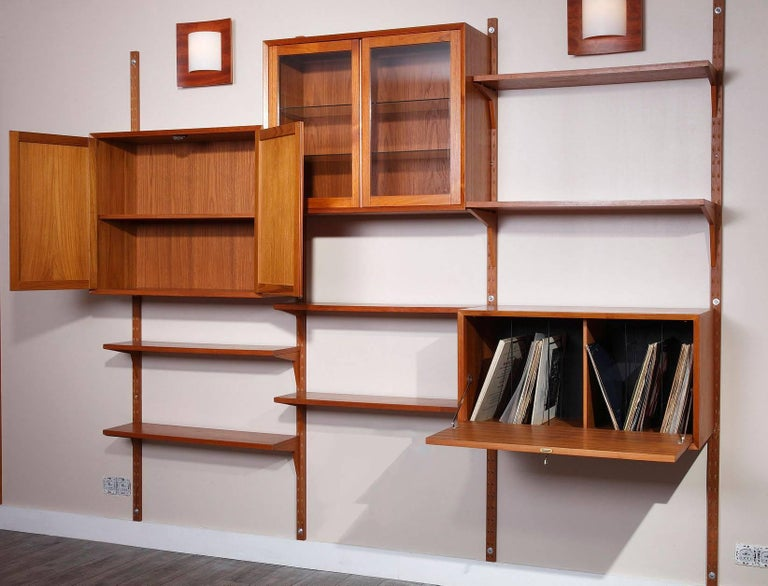 Modular wall system designed by Poul Cadovius in the 1950s, crafted in teak, provided with wooden fixations. It is composed of four vertical ladders with six shelves and three containers as follow: One container with lateral doors, one container
