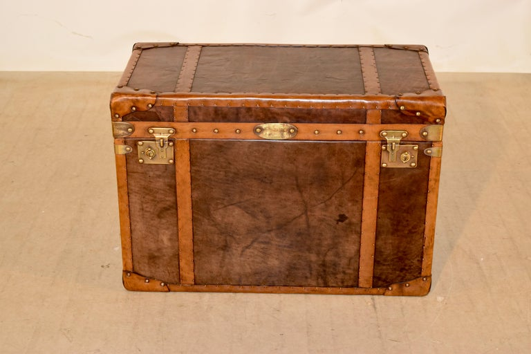 Early 20th century English steamer trunk which has been completely refurbished. The exterior features contrasting colors of leather with brass nail decoration, along with brass hardware and new interior lining.