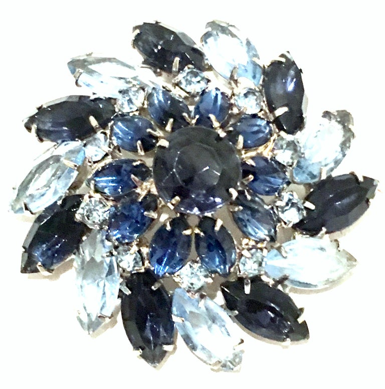 Mid-20th Century Silver Plate & Austrian Crystal Dimensional Abstract Floral Brooch. This silver rhodium plate brooch features fancy prong set brilliant cut and faceted sapphire blue navette and round stones. The light blue sapphire navette stones
