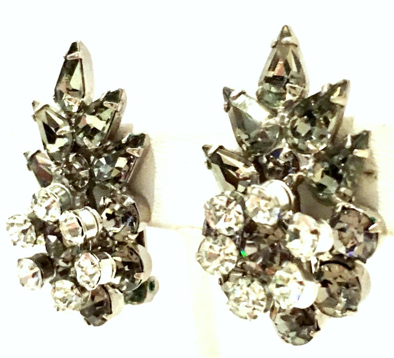 Mid-20th Century Pair Of Silver & Austrian Crystal Dimensional Earrings. These clip style dimensional abstract floral earrings feature silver plate base metal  with brilliant cut and faceted fancy prong set