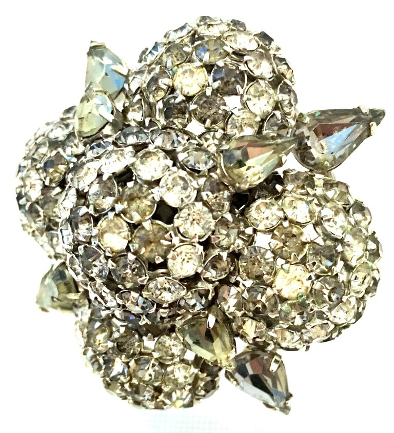 20th Century Art Deco Style Silver & Austrian Crystal Dimensional Starburst Brooch By, Warner. This finely crafted highly dimensional silver and Austrian crystal brooch features brilliant cut and faceted fancy prong set colorless, smoky and sage