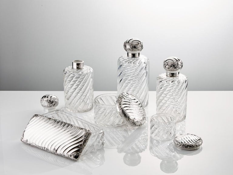 """This stunning quality dressing table set of oversized perfume bottles are in excellent condition the silver tops and jar lids are perfectly matched with the glass which has this fluid swirling design.  Largest Bottle - height 10 1/4"""". base diameter"""