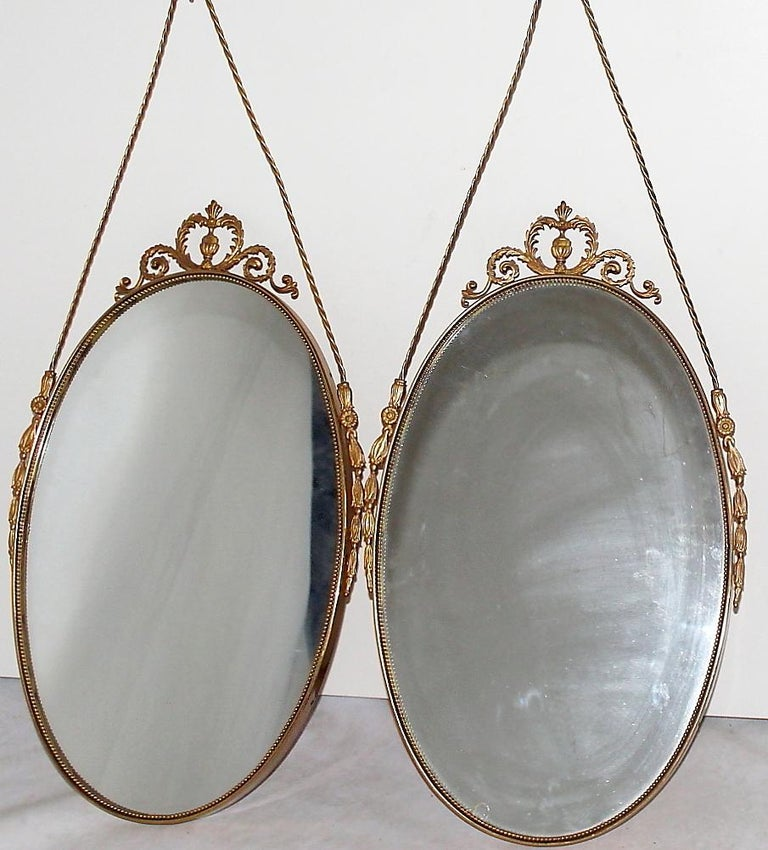 A small Swedish Art Deco pair of wall mirrors made of hand crafted brass and mirrored glass. The vintage pair is in good condition, enhanced by detailed brass décor. Minor losses on the original glass. Wear consistent with age and use. Circa 1930,