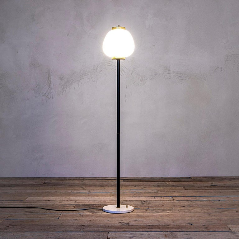 Floor lamp designed by Stilnovo in 1950s with structure in lacquered metal, diffuser in satin glass and brass and circular base in white marble. The lamp can be switched on/of by a button on its marble base. Very good condition, fully original and