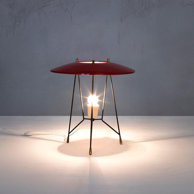 Verypeculiar table lamp produced by Stilnovo in '50s. The lamp has a three-leg structure in metal, its diffuser as well is in red lacquered metal, details in brass. Fully working, original in all its parts,