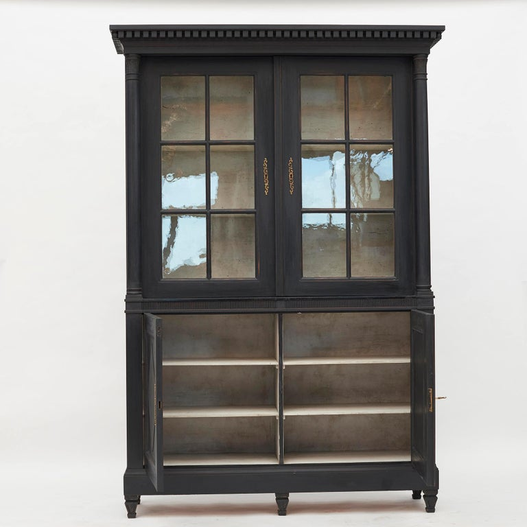 A Beautiful Gustavian 4-doors glass and wood cabinet. Pair of locking paned glass doors sitting atop pair of locking wood doors with rhombus motif fillings. Black painted wood with light grey color inside. Brass fittings, 1 key. Gustavian style,