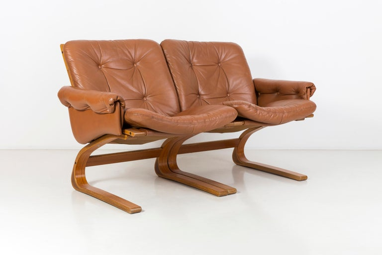 Norwegian Kengu sofa made by the Rybo Rykken manufacture, whose designers are Elsa & Nordahl Solheim. It was produced in 1976. The frame of the sofa is made of bent teak wood. The upholstery is original, made of genuine leather. This sofa is an icon