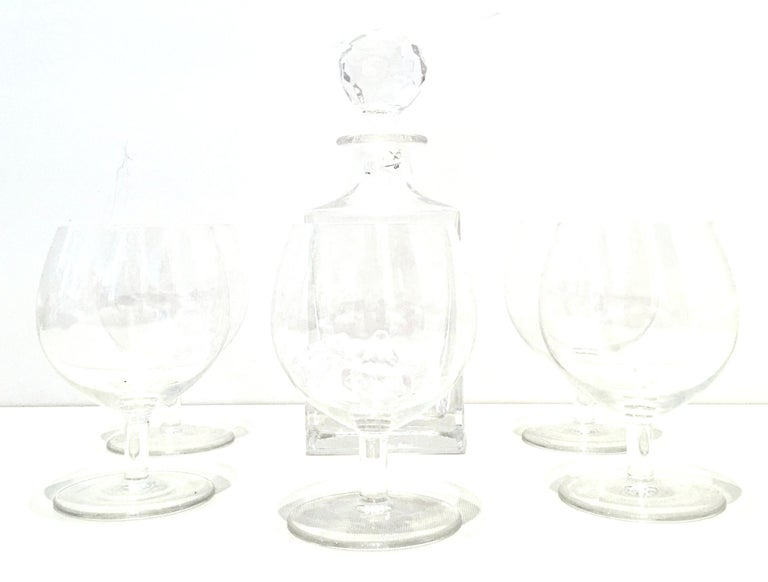 20th century cut crystal liquor decanter and crystal stem drink glasses by, Tiffany & Co. and Riedel. This six-piece set includes one Tiffany & Co. liquor decanter with stopper and five crystal stem drink glasses by, Riedel. Each piece is