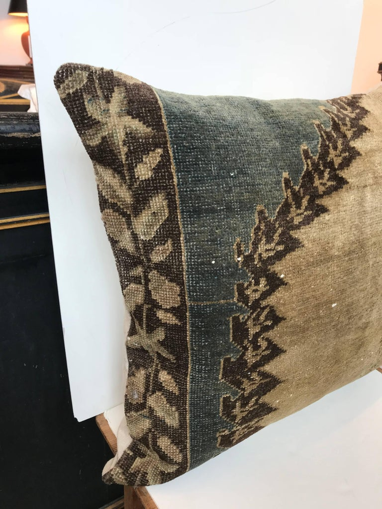 20th century Turkish green and khaki rug pillow; Crafted from a rug fragment. Down insert. Zipper closure with cotton back.