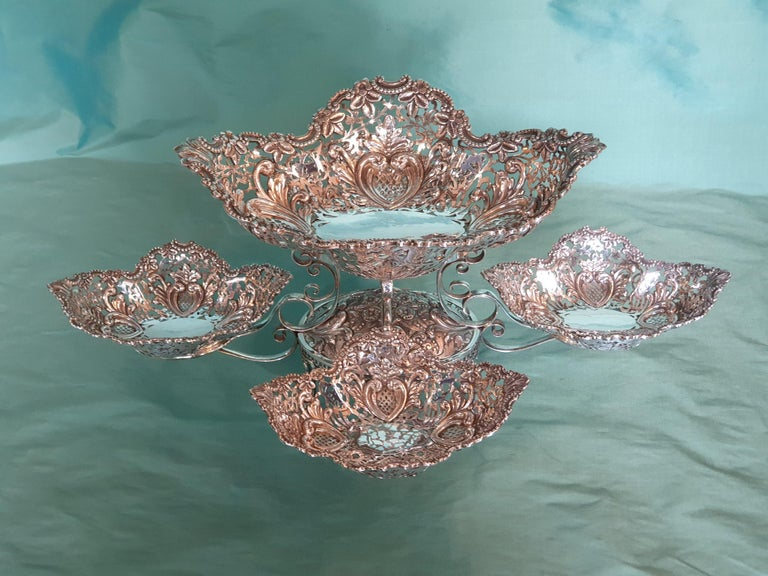 A remarkable Victorian style handcrafted chiseled sterling silver epergne by Italian silversmith Argenteria Auge from Milan. The entire epergne is beautifully embellished with flowers, leaves and hearts.  Epergnes have been a lasting symbol of