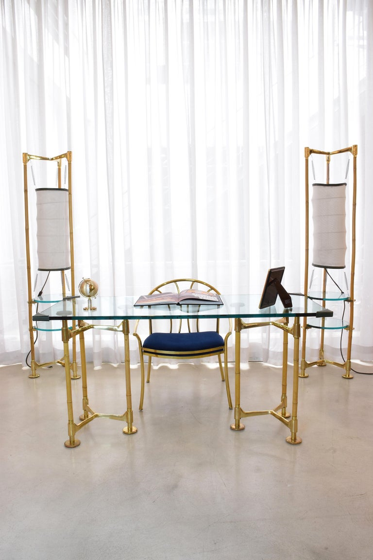 A stunning 20th century vintage rectangular desk composed of two tripod feet built out of gold polished brass and bamboo with circular disk endings. The tabletop is a 2cm thick glass and is adorned with leather stitched endings for