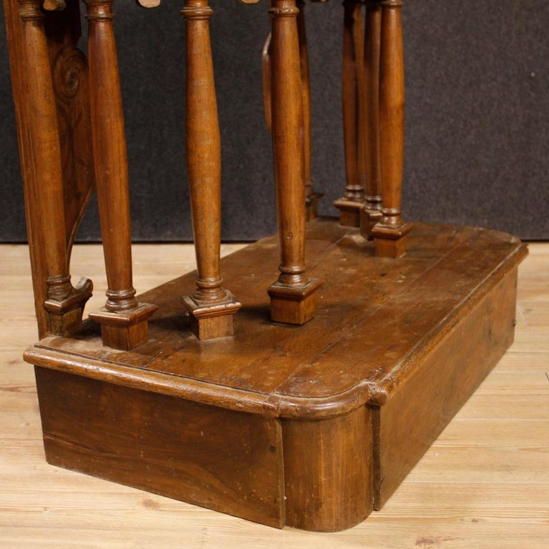 Italian kneeling-stool composed of antique elements (from 17th century) and other elements from 20th century. Furniture carved in walnut wood adorned with 6 columns and two half columns in the back. Furniture equipped with a drawer with a working