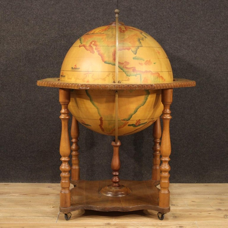 Great Italian bar cabinet from the 1960s-1970s. Alcohol stand built in the shape of a globe in wood and metal with applied paper. Furniture supported by four solid legs resting on wheels, ideal to be placed in a living room or studio of beautiful