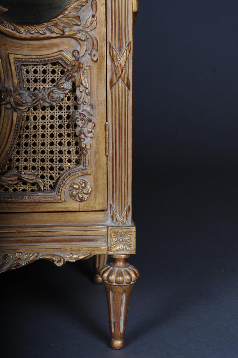 Solid beech, gilded. Rectangular, three-sided, faceted beveled, one-door body on conical legs. The door is partially provided with wickerwork. The front, corners and sides are decorated with carved, classic elements such as garlands and bows.