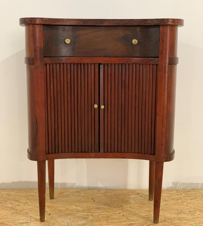 A French oak bedside tables with  reeded sliding-doors and drawer , from the late 19th century. This French 'table de chevet' features a kidney shape top sitting above two reeded sliding doors flanking one small size dovetailed drawers, all opening