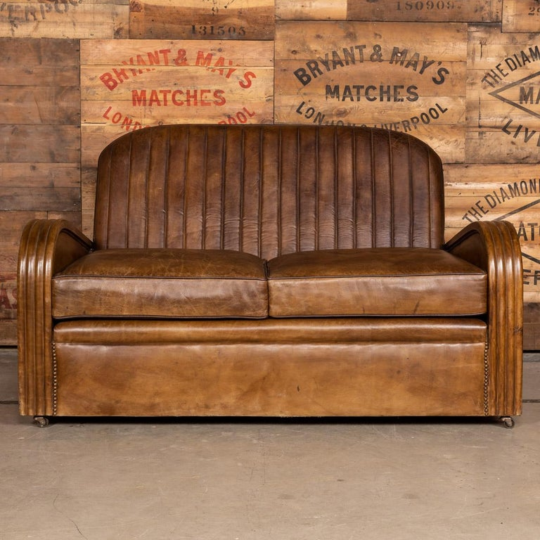 Antique early 20th century Art Deco suite, consisting of a pair of matching tub chairs and a sofa. Showing superb patina and color, this wonderful pair of club chairs were hand upholstered sheepskin leather by the finest craftsmen and mounted with