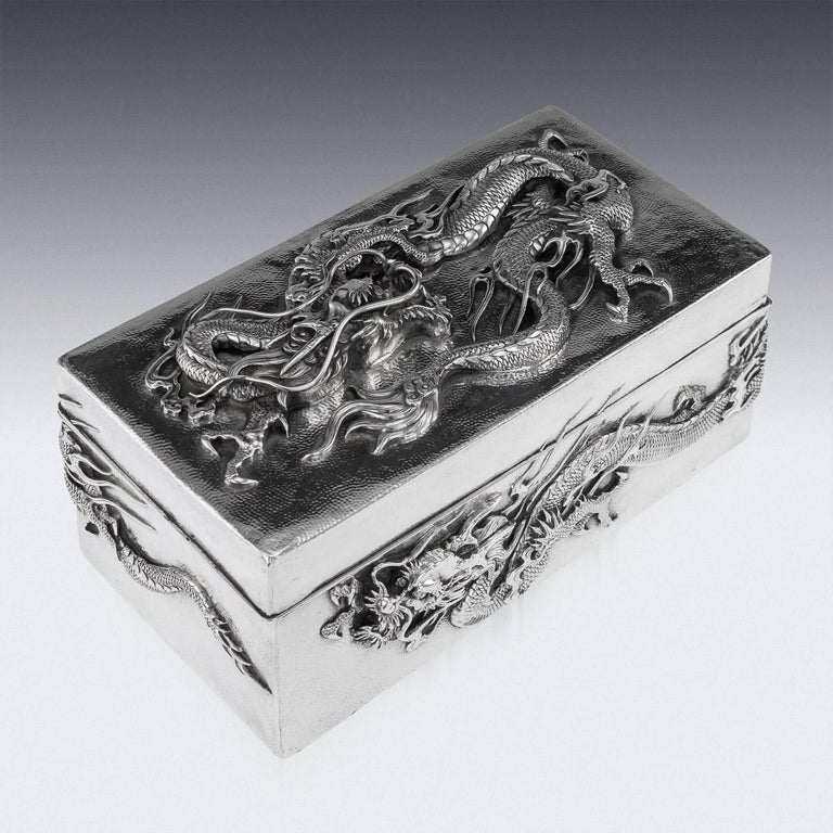 Antique early 20th century Japanese Meiji period solid silver cigar box, double skinned body, sides and lid are embossed in high-relief with water dragons and applied with flowing whiskers on hand hammered ground, dark wood lined base and interior.