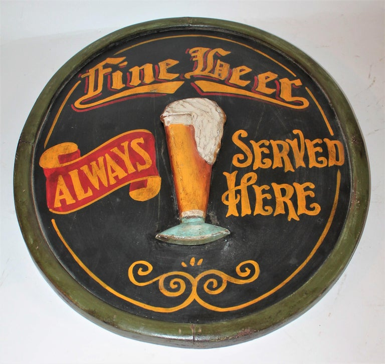 This fun and folky beer sign is hand carved and painted wood with a carved out beer mug. The condition is very good with wear in areas. This oval sign id decorative and great for a bar in your home.