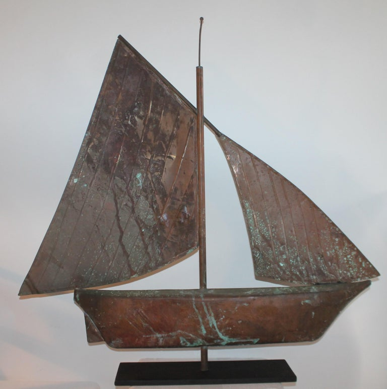 Early 20th century copper sailboat weather vane with amazing patina to the body and sail. This sailboat weather vane has a custom made iron base. Would make for a stunning mantel (fireplace) piece or center piece.
