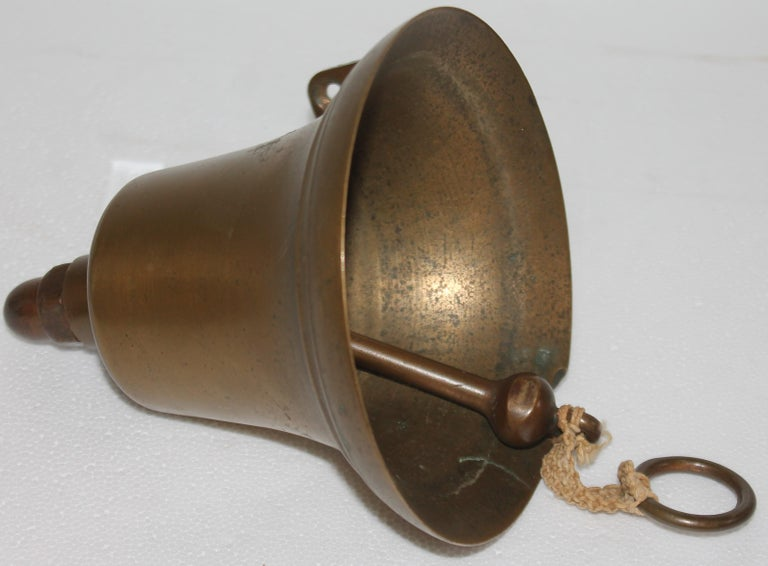 20thc Ships brass bell with rope for a ringer. This could be a dinner bell on the front of a house or mounted on the front of the house.