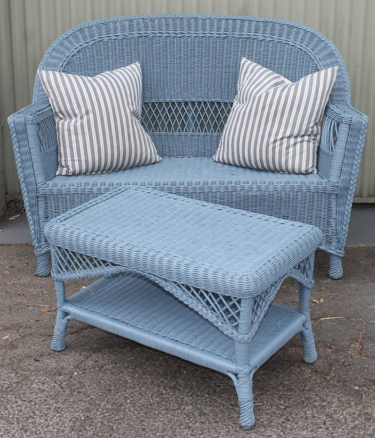 This fine wicker painted sofa and wedge wood blue & matching coffee table & end table all in very good condition. The set is unmarked and looks like Haywood Wakefield style. The three piece set is priced as a set. Settee measures - 52 wide x 36