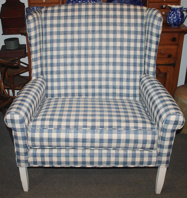 This fantastic wing back love seat is in amazing condition and great form. The repro. blue & cream homespun linen upholstered love seat is amazing. The new fabric looks like early 19thc fabric. The frame is in a worn white paint. The cushion has a