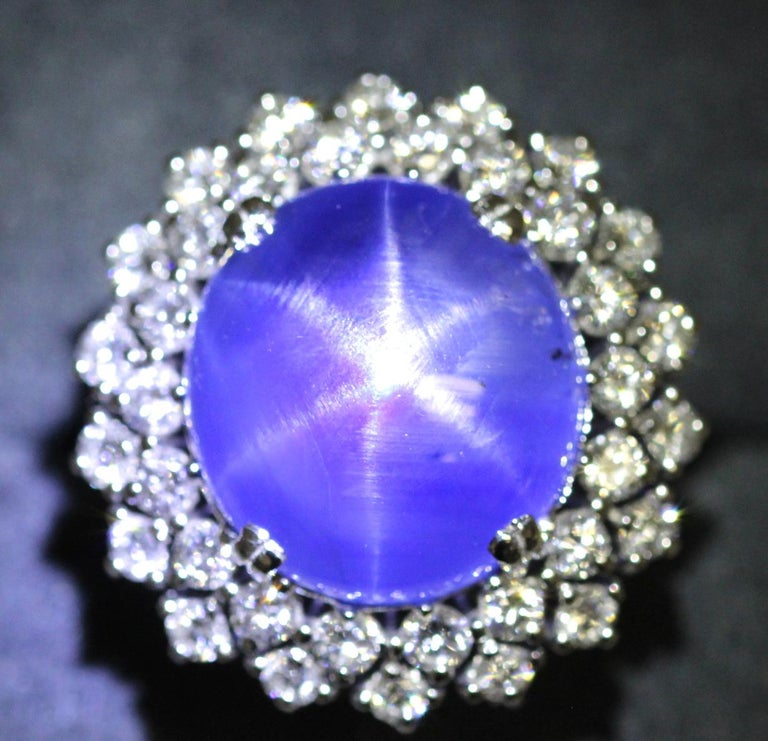 A 1980's Vintage star sapphire and diamond ring. This cocktail ring features a natural, no treatment Ceylon star sapphire weighing approximately 21 carats. The Star sapphire is round domed cabochon shape with a rich cornflower blue appearance. We