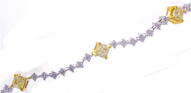 This beautiful bracelet is crafted in 14-karat Two Tone Gold. It features 8 glistening cushion cut yellow Diamonds 2.11 Carat - SI quality, connected by 56 white Round Diamonds 1.20 Carat GH-SI quality. This bracelet is 7.5