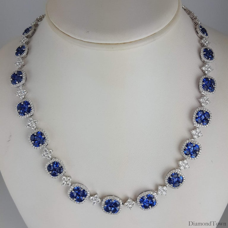 This impressive necklace features fifteen blue sapphire clusters, each inside a halo of round diamonds, and alternating with square clusters of round white diamonds. Additional diamond clusters extend to the back of the necklace.  Each sapphire