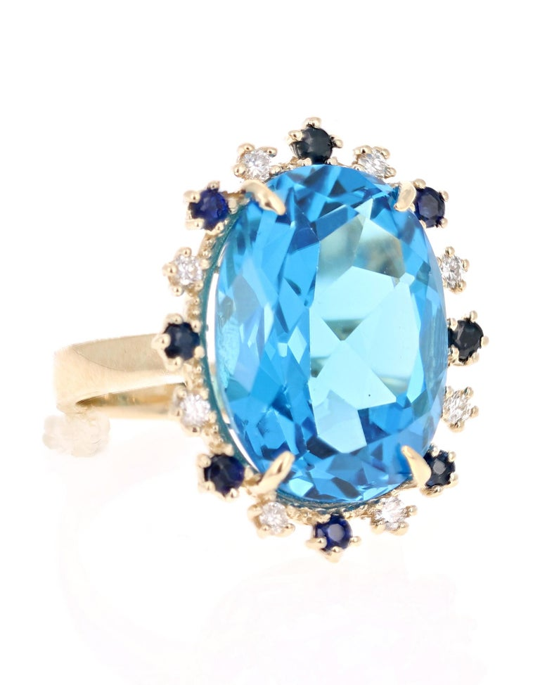 Beautiful to say the Least! This magnificent Oval cut 20.73 Carat Blue Topaz is surrounded by 8 Round Cut Diamonds that weigh 0.25 Carats (Clarity: SI, Color: F) and 8 Blue Sapphires that weigh 0.52 Carats. The total carat weight of the ring is