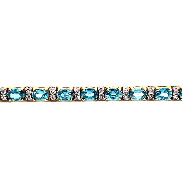 This stunning Blue Zircon and Diamond Bracelet features 18 Beautiful Oval Blue Zircons, each separated by set of 2 Radiant Round White Diamonds. This Bracelet is set in 14K Yellow and White Gold, Yellow Gold Baskets for the Blue Zircons and White