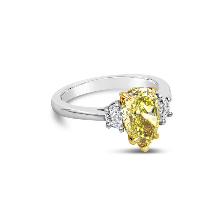 Showcasing a 2.18 carat pear shape diamond center stone certified by GIA as fancy intense yellow color. Flanking the center are two half moon diamonds weighing 0.33 carats total. Made in platinum.  Style available in different price ranges. Prices