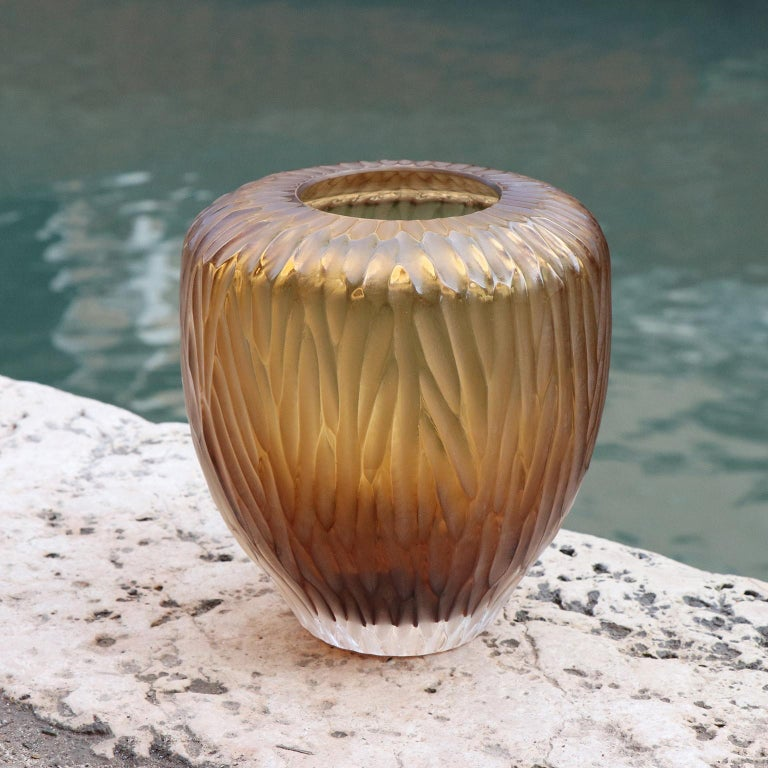 Inspired by the ancient amphorae, this vase resembles the elongated form of a drop, which in Italian translates as Goccia. Following the blowing process the vase is engraved and polished producing a vibrant faceted surface.  This vase is