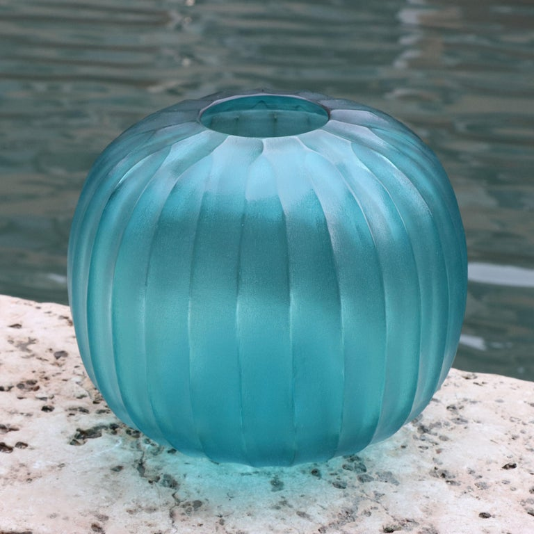 The melted glass is first blown in the heat of the furnace and shaped into a round vase with a small opening. Once solid the glass is cold carved to produce the linear cuts which mark its surface reminding us of the shell of a sea urchin,