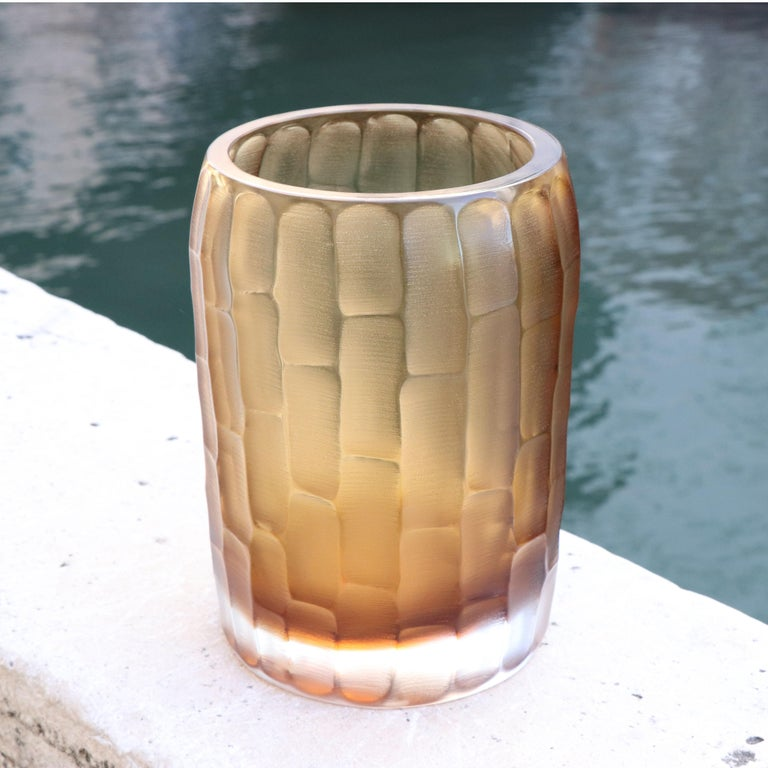 The name Rullo evokes the act of rolling the heated glass on the blow pipe. This small vase is first shaped by blowing the molten glass and further modelled by carving the surface once cooled. The vibrations of the light on the etched surface are