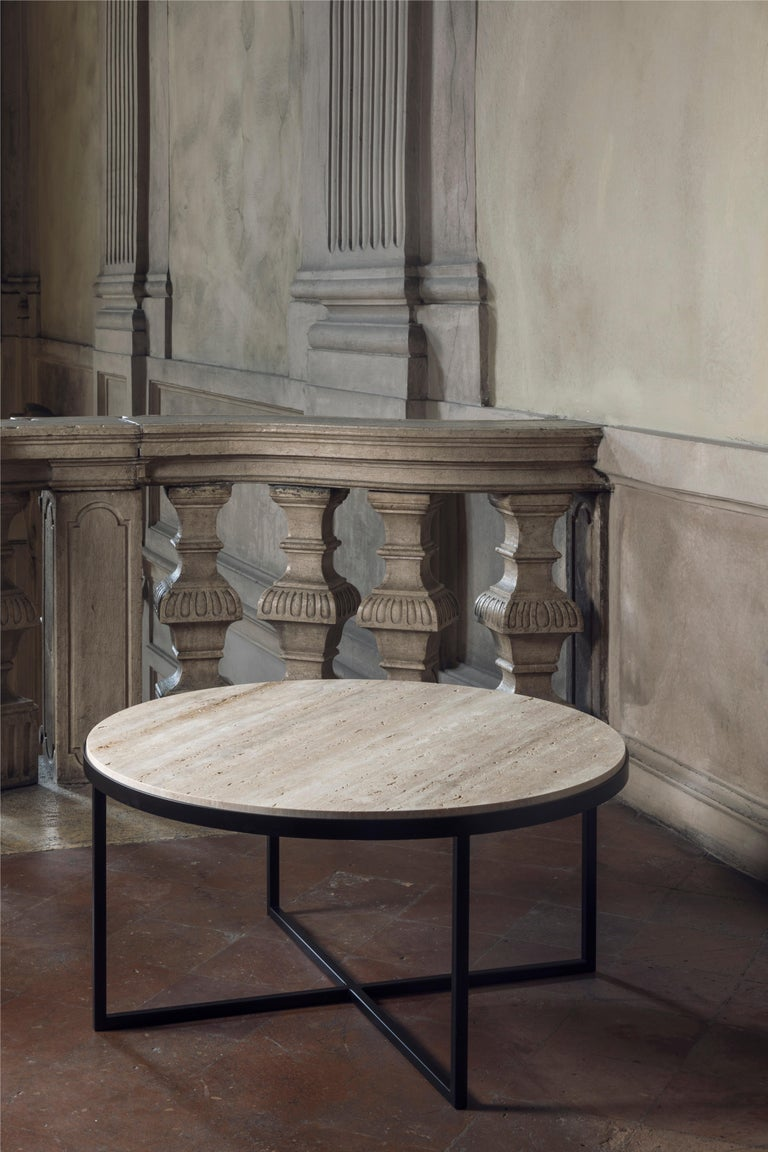 An essential perfection characterizes this coffee table, called Eclipse. The severity of the geometry of the structure, emphasized by the iron, is counterbalanced by the precious top in travertino, lying on the structure like a perfect round